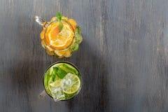 两块玻璃玻璃用从石灰和柠檬的自创柠檬水在土气黑木背景 库存图片