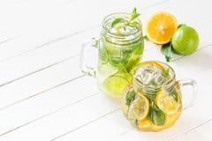 两块玻璃玻璃用从石灰和柠檬,在白色木土气背景的被切的柑橘的自创柠檬水 库存图片