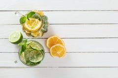两块玻璃玻璃用从石灰和柠檬,在白色木土气背景的被切的柑橘的自创柠檬水 图库摄影