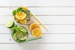 两块玻璃玻璃用从石灰和柠檬,鸡尾酒管的自创柠檬水,切了柑橘和薄菏在白色木头 免版税库存图片