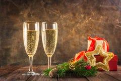 两块玻璃用冷杉的香槟和构成分支,礼物盒,并且光亮的衣服饰物之小金属片担任主角在木桌上的装饰与金黄 免版税库存图片