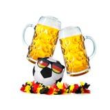 两块玻璃用啤酒和与德国爱好者太阳镜的足球 库存图片