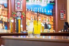 两块玻璃用柠檬水-柠檬,橙色 在酒吧和餐馆的背景 免版税图库摄影