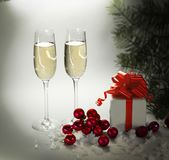 两块玻璃用香槟和箱子有礼物的在圣诞节b 库存照片