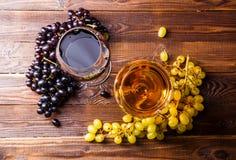 两块玻璃的图象用汁液,葡萄,在木桌上, 免版税库存图片