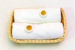 两块白色毛巾和小肥皂在柳条筐,好accommod 免版税库存照片