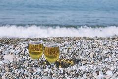 两块美丽的玻璃用在小卵石的清淡的茶点在Th 免版税库存图片