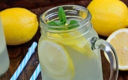 两块金属螺盖玻璃瓶玻璃用在桌上的柠檬水 免版税库存图片