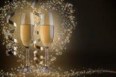 两块香槟玻璃,在金黄bokeh背景 免版税图库摄影