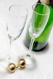 两块玻璃、一个瓶香槟和金子圣诞节球clos 免版税库存照片