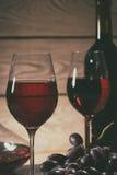 两块玻璃和一个瓶红葡萄酒和葡萄在桌上 库存图片