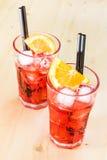 两块玻璃喷开胃酒与橙色切片和冰块的aperol鸡尾酒在木桌上 免版税库存照片