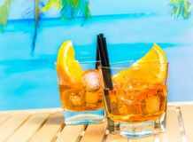 两块玻璃喷开胃酒与橙色切片和冰块的aperol鸡尾酒在迷离海滩和棕榈背景 图库摄影