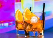 两块玻璃喷开胃酒与橙色切片和冰块的aperol鸡尾酒在酒吧桌,迪斯科大气背景上 免版税库存照片