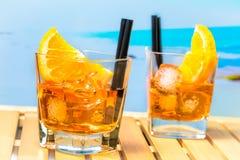两块玻璃喷开胃酒与橙色切片的aperol鸡尾酒,并且在迷离的冰块使背景靠岸 免版税库存照片