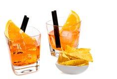 两块玻璃在炸玉米饼芯片附近喷开胃酒与橙色切片和冰块的aperol鸡尾酒 免版税图库摄影