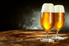 两块玻璃有很多在桌上的啤酒 免版税库存照片