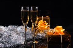 两块玻璃有很多香槟和两个礼物盒 免版税库存照片