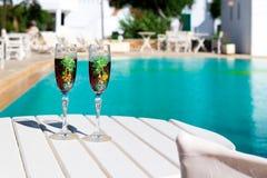 两块玻璃用在一张白色桌上的酒在水池附近 免版税库存照片