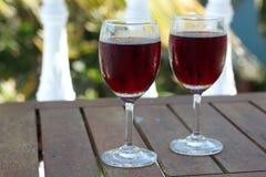 两块玻璃用在桌上的红葡萄酒 免版税库存照片