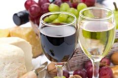 两块玻璃用白色和红葡萄酒、乳酪和葡萄 库存照片