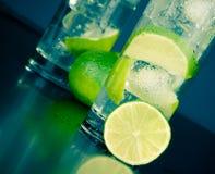 两块玻璃细节与鸡尾酒的,在桌上的冰和石灰切片 免版税图库摄影