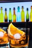 两块玻璃细节喷开胃酒与橙色切片和冰块的aperol鸡尾酒在酒吧桌,迪斯科大气backgroun上 库存照片
