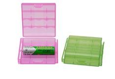 两塑料电池持有人和一个电池在白色 免版税库存图片