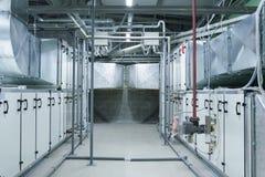两处理单位的灰色工业空气在有大大小通风管和管道的透气植物屋子 免版税库存图片