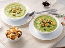 两大白色碗用硬花甘蓝,夏南瓜,在白色背景,侧视图的绿豆菜绿色奶油色汤  免版税图库摄影