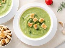 两大白色碗用硬花甘蓝,夏南瓜,在白色背景,顶视图的绿豆菜绿色奶油色汤  库存照片