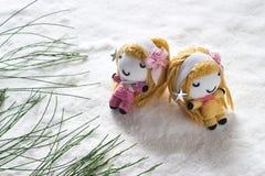两天使在圣诞节,玩偶手工制造概念前放松在雪的睡眠 免版税图库摄影