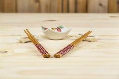 两套剁棍子、持有人和调味汁在杉木桌上滚保龄球 库存图片