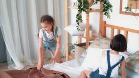 两女孩做床,被投入的枕头,有毯子的盖子,慢动作 股票录像