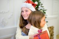 两女孩,礼物,圣诞树,红色帽子 图库摄影