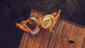 两女性松弛近的河 免版税库存图片