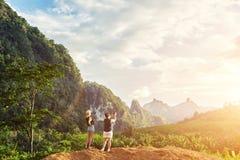 两女性站立反对密林与拷贝空间的风景和多云天空背景 免版税库存照片