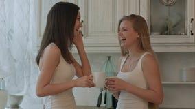 两女朋友用电话饮用的咖啡或绿茶在厨房内部背景 库存图片