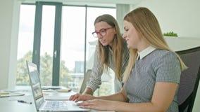 两妇女谈论想法使用膝上型计算机 库存图片