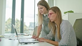 两妇女谈论想法使用膝上型计算机 免版税库存照片