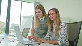 两妇女谈论想法使用膝上型计算机 免版税图库摄影