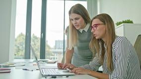 两妇女谈论想法使用膝上型计算机 库存照片