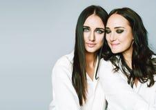 两姐妹孪生摆在,做照片,穿戴了同样白色衬衣 免版税库存照片