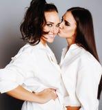 两姐妹孪生摆在,做照片selfie,穿戴了同样白色衬衣,微笑不同的发型的朋友紧密  免版税库存图片