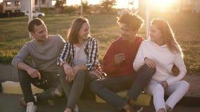 两对年轻人混合的族种夫妇坐在街道上的遏制 一起微笑,愉快的年轻人有的outdors时间 股票录像