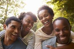 两对成人黑夫妇获得扛在肩上的乐趣,接近  免版税库存照片