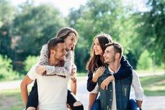 两对爱恋的夫妇扛在肩上获得乐趣户外 免版税图库摄影