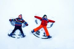 两小兄弟姐妹哄骗做雪天使的五颜六色的冬天衣裳的男孩,放下在雪 免版税图库摄影