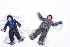 两小兄弟姐妹哄骗做s的五颜六色的冬天衣裳的男孩 免版税库存照片