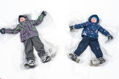 两小兄弟姐妹哄骗做s的五颜六色的冬天衣裳的男孩 图库摄影